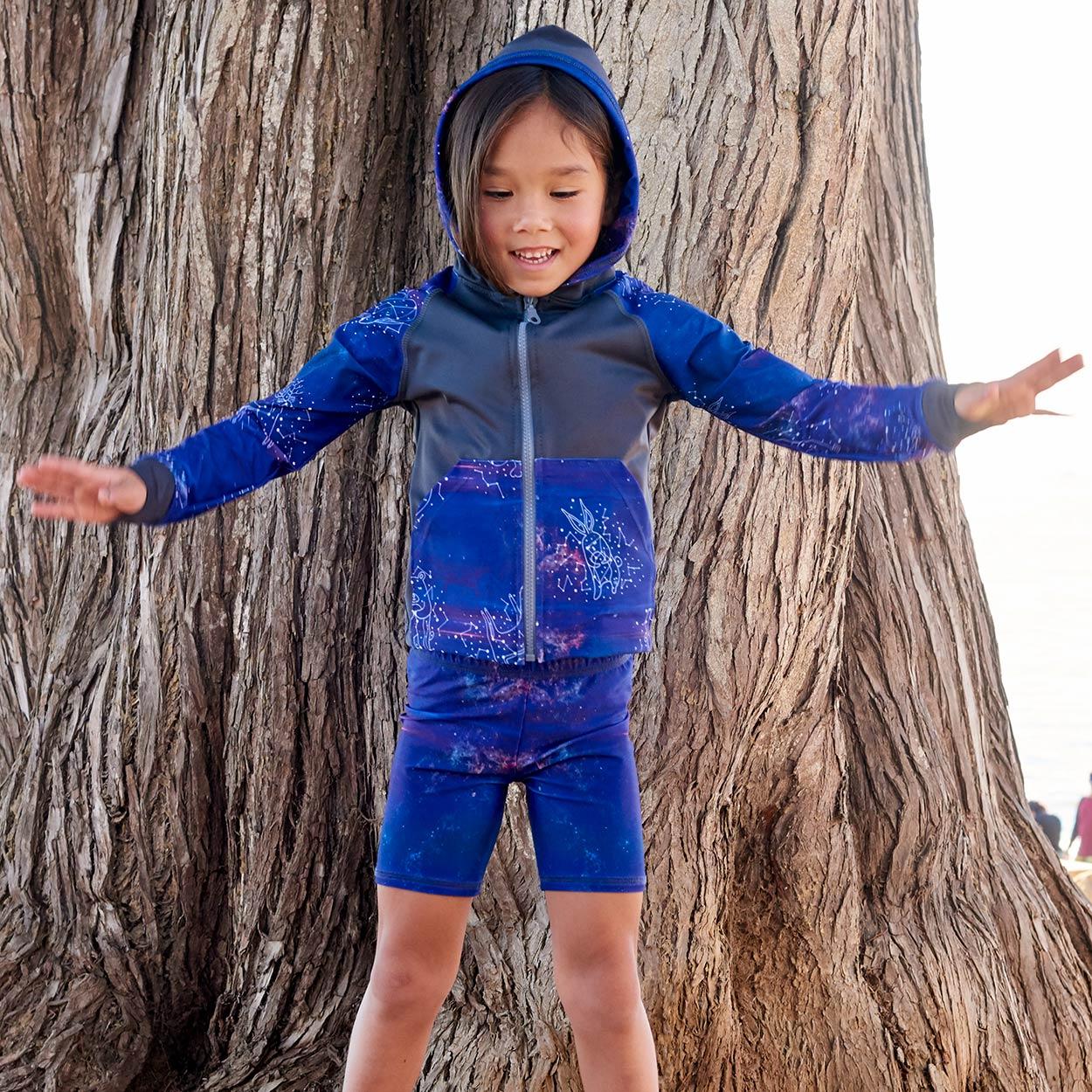 Cosmos Sunblocker Shorts Upf50 Kids Boys Girls Size 2 12 Purple Unisex Girl On The Beach Balancing On Tree Roots Sunpoplife