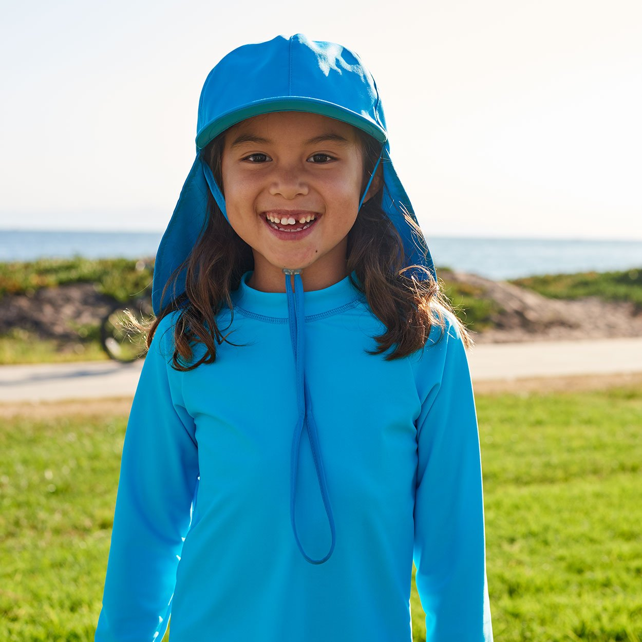 Kids Blue Legionnaire Sun Hat Upf 50 Size S Xl Girl Smiling Wearing Blue Hat on a Grassy Patch Sunpoplife