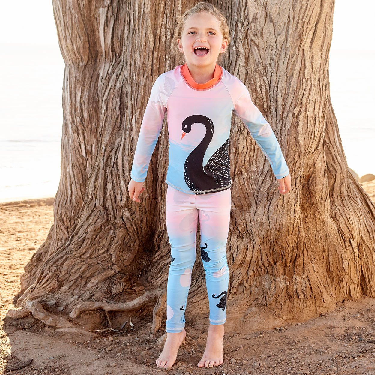 Swans Sunblocker Leggings Upf50 Girls Size 2 6 Peach Aqua Happy Girl On Her Tippy Toes In Front Of A Tree By The Beach Sunpoplife